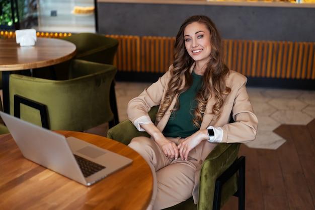 Mulher de negócios dona de restaurante usa laptop vestido elegante macacão sentado na mesa no restaurante com superfície do balcão de bar caucasiano feminino pessoa de negócios interna