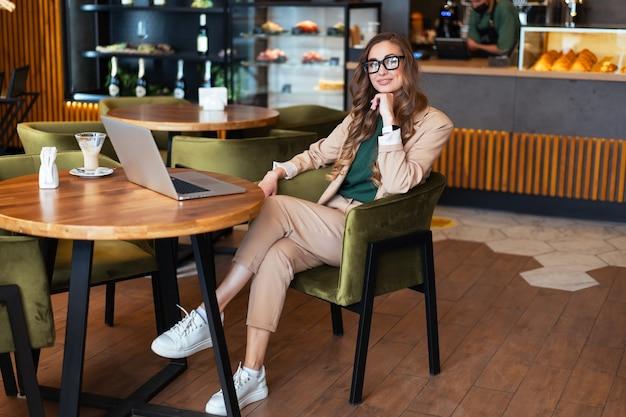 Mulher de negócios dona de restaurante usar laptop vestido elegante macacão sentado na mesa no restaurante com balcão de bar caucasiano feminino pessoa de negócios comprimento total interno