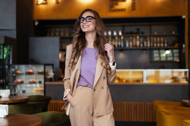 Mulher de negócios dona de restaurante vestida de elegante macacão em pé no restaurante com balcão de bar branco óculos feminino pessoa de negócios com as mãos nos bolsos