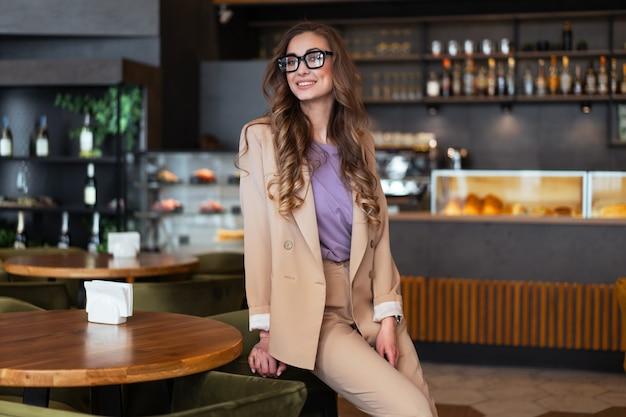 Mulher de negócios, dona de restaurante, vestida de elegante macacão, em pé no restaurante com balcão de bar, branco óculos feminino pessoa de negócios com as mãos nos bolsos