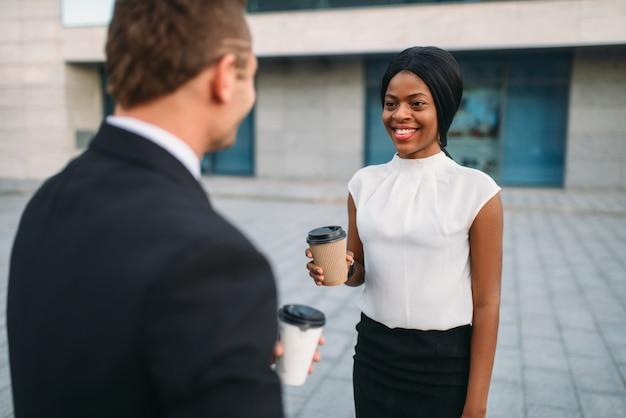 Mulher de negócios e empresário com xícaras de café, encontro ao ar livre de parceiros, prédio de escritórios moderno