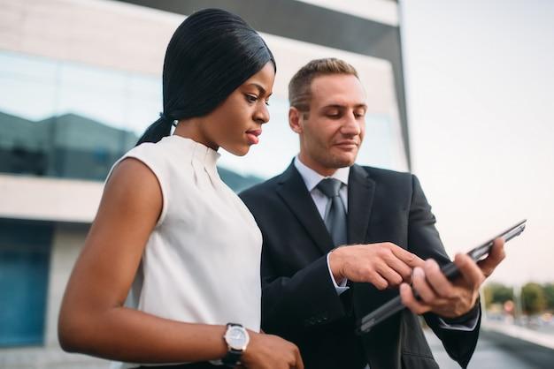 Mulher de negócios e empresário olhando para a tela do laptop, reunião de sócios ao ar livre, prédio de escritórios moderno