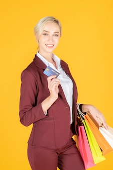 Mulher de negócios é feliz com as compras em fundo amarelo studio