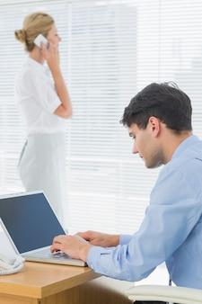 Mulher de negócios e homem usando celular e laptop no escritório
