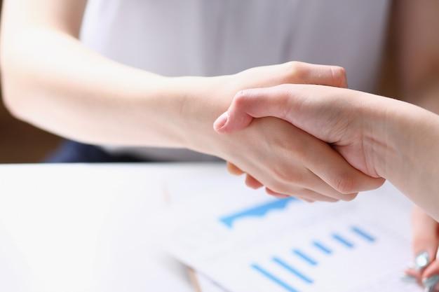 Mulher de negócios e mulher apertam as mãos