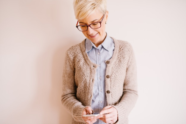 Mulher de negócios elegante bonita no colete de suéter usando um móvel perto da parede branca.