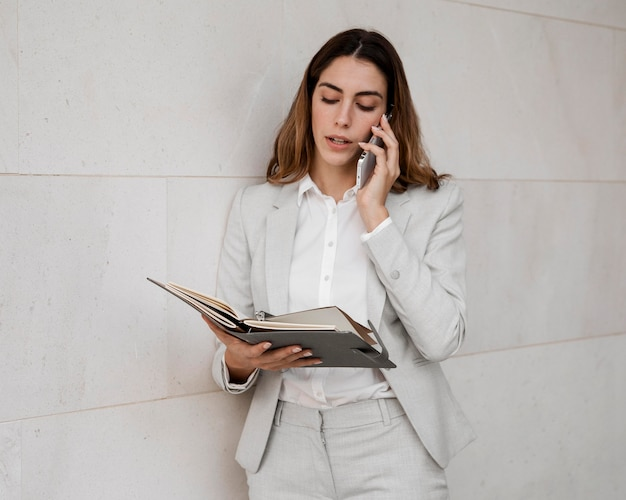 Mulher de negócios elegante com agenda falando ao telefone