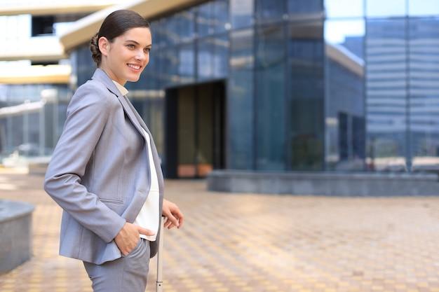 Mulher de negócios elegante com bagagem no aeroporto. mulher de negócios com mala indo para viagem de negócios.