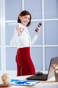 Mulher de negócios elegante com telefone mostra sinal ok no escritório.