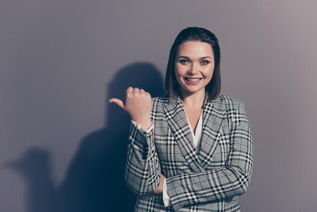 Mulher de negócios elegante com um blazer xadrez posando dentro de casa