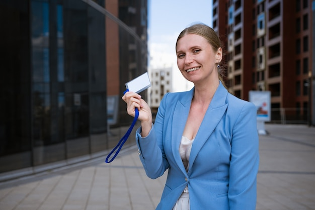 Mulher de negócios elegante com uma jaqueta azul segura um distintivo na mão contra a parede de um prédio de escritórios