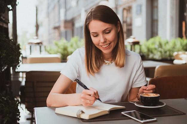 Mulher de negócios elegante em um café de rua fazendo anotações em um caderno e bebendo café