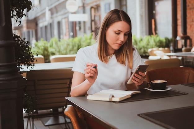 Mulher de negócios elegante em um café de rua fazendo anotações em um caderno e enviando mensagens ao telefone