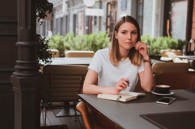 Mulher de negócios elegante em um café de rua fazendo anotações em um caderno