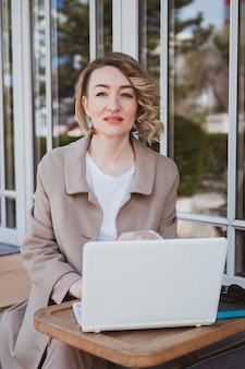 Mulher de negócios elegante em um café de rua trabalhando em um laptop