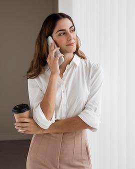 Mulher de negócios elegante falando ao telefone enquanto segura a xícara de café