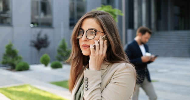 Mulher de negócios elegante jovem caucasiana de óculos falando no celular na rua. linda mulher falando no celular ao ar livre. mulher atraente em óculos, tendo o telefonema. conversação.