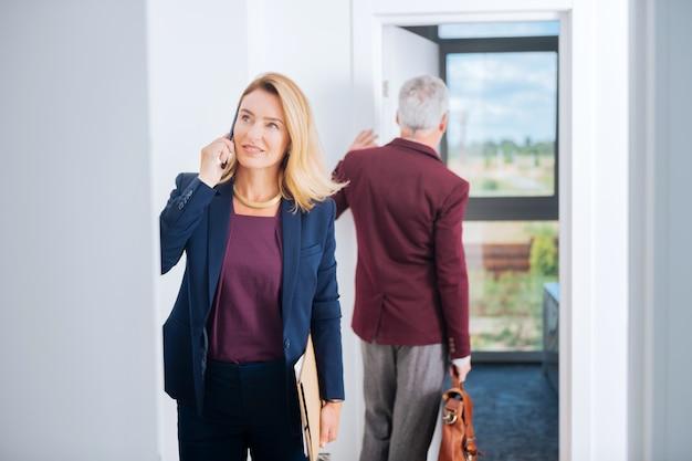 Mulher de negócios elegante. mulher de negócios bonita e elegante recebendo uma ligação importante de seu parceiro enquanto estava no centro de negócios