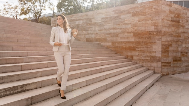 Mulher de negócios elegante na escada ao ar livre com smartphone e espaço de cópia