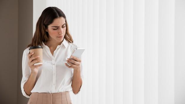 Mulher de negócios elegante usando smartphone enquanto segura a xícara de café com espaço de cópia