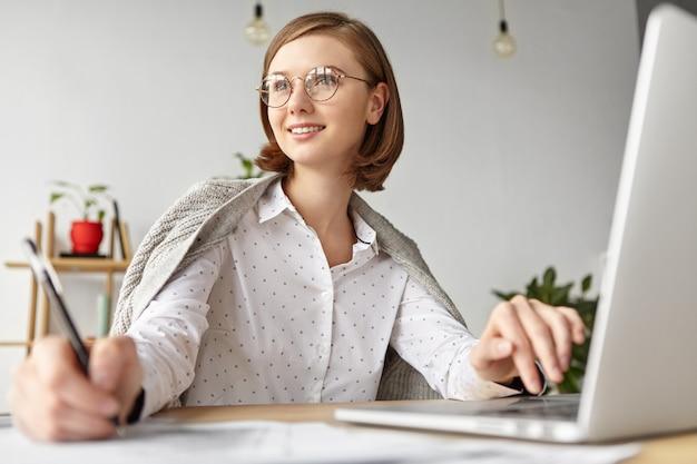 Mulher de negócios elegante vestida formalmente sentada com um laptop