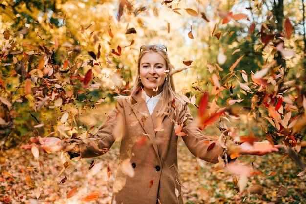 Mulher de negócios elegante vestido jovem jogando no estádio. diversão de outono. loira alegre feliz menina de casaco vomitando maple folhas ao ar livre.