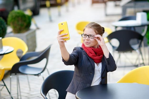 Mulher de negócios em copos, sentado em uma mesa em um café e faz selfie