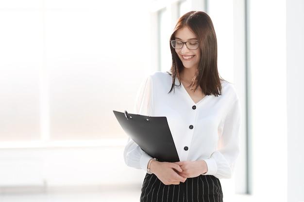 Mulher de negócios em pé em um escritório bem iluminado