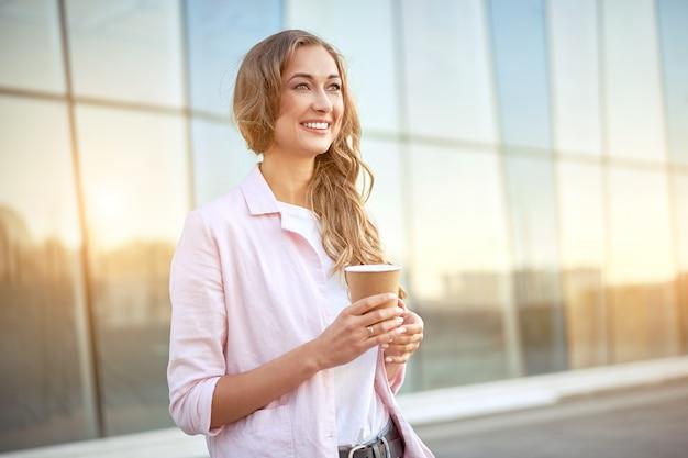 Mulher de negócios em pé no dia de verão perto do prédio corporativo. pessoa de negócios