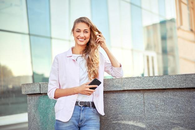 Mulher de negócios em pé no dia de verão perto do prédio corporativo.