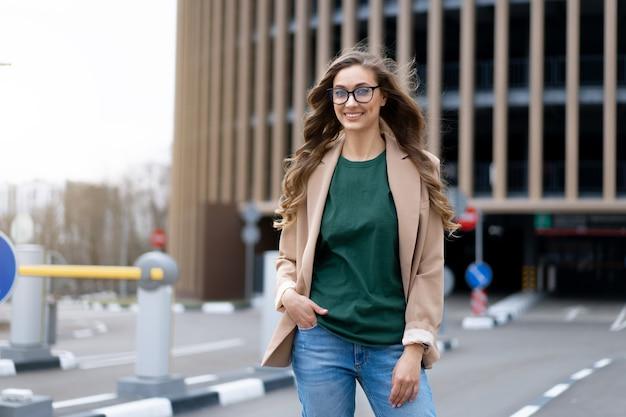 Mulher de negócios em pé perto da garagem de estacionamento coberta mulher de meia-idade caucasiana em óculos ao ar livre pessoa de negócios