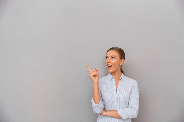 Mulher de negócios em pé sobre o fundo da parede cinza posando apontando para copyspace.