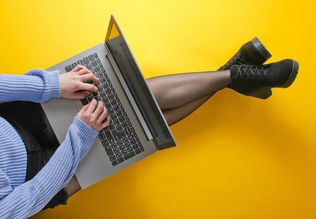 Mulher de negócios em shorts, calças justas e botas está digitando em um laptop enquanto está sentado no chão amarelo. freelancer, blogueiro, conceito de trabalhador on-line