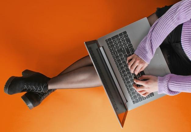 Mulher de negócios em shorts, meia-calça e botas está digitando em um laptop enquanto está sentado em um fundo laranja.