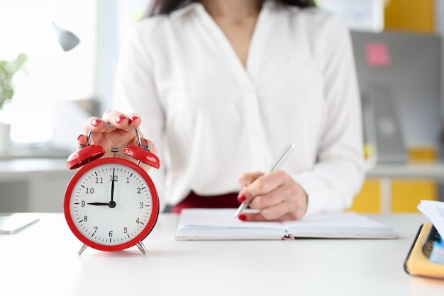 Mulher de negócios em sua mesa segura a mão no despertador vermelho e faz anotações no diário