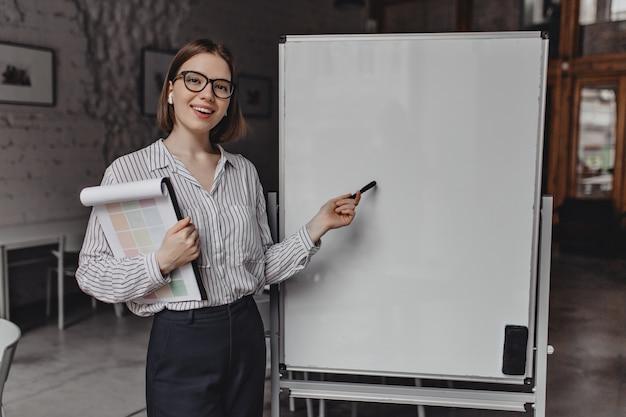 Mulher de negócios em terno estrito e óculos sorri, segura documentos e aponta para o quadro de escritório branco.
