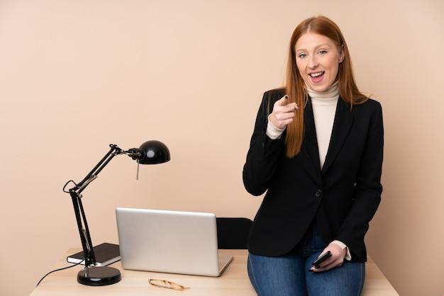 Mulher de negócios em um escritório aponta o dedo para você