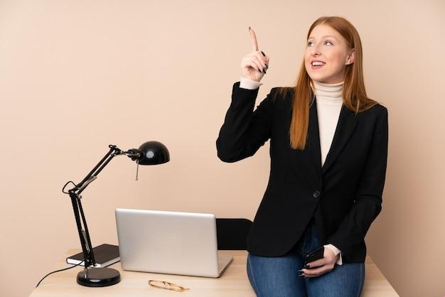 Mulher de negócios em um escritório, apontando com o dedo indicador uma ótima idéia