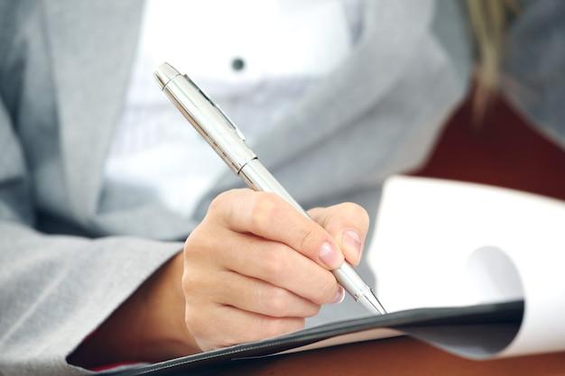 Mulher de negócios em um terno escrevendo notas com uma caneta no papel de documento