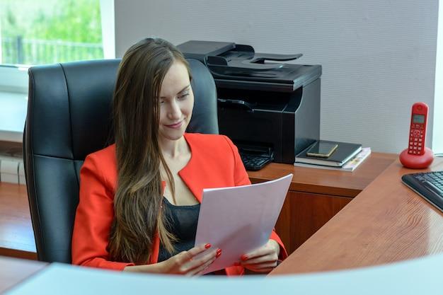 Mulher de negócios em um terno vermelho senta-se em uma cadeira de couro e lendo um contrato