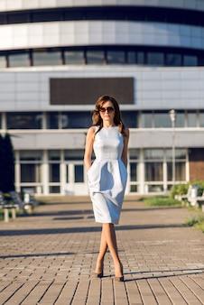 Mulher de negócios em um vestido, andando pela cidade