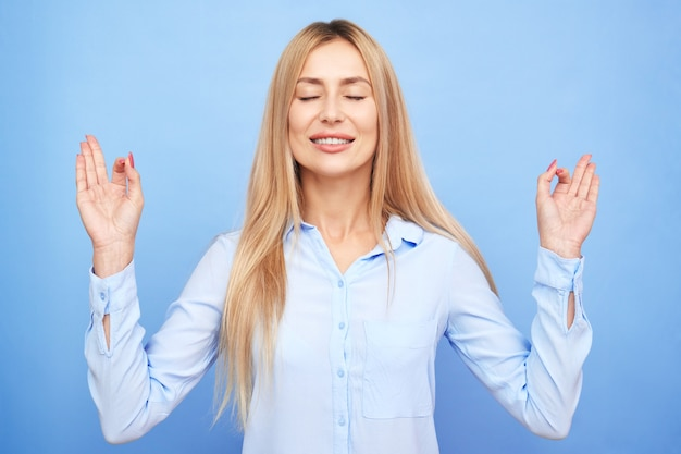 Mulher de negócios em uma camisa azul mantém os olhos fechados segurando os dedos em um gesto de mudra, a bela gerente mantém a calma relaxa isolada no fundo azul, meditação com terapia antiestresse