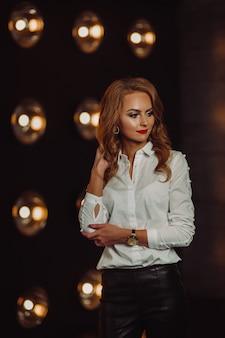 Mulher de negócios em uma camisa branca no contexto de lâmpadas acesas no interior de um escuro studio.model com cabelo comprido e batom vermelho.