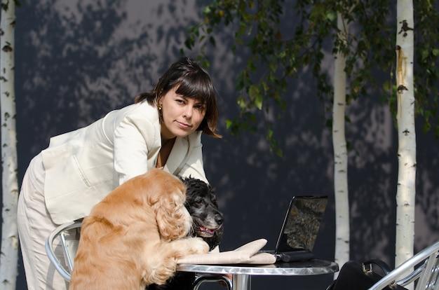 Mulher de negócios em uma reunião de conferência com dois cães cocker spaniel
