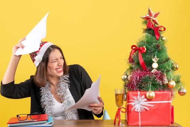 Mulher de negócios emocional em um terno com chapéu de papai noel e decorações de ano novo segurando documentos e sentada em uma mesa com uma árvore de natal no escritório