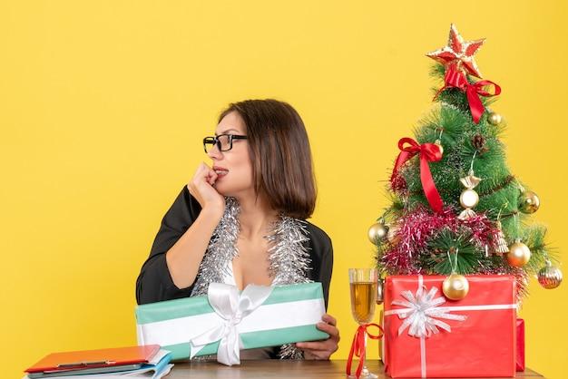 Mulher de negócios emocional em um terno com óculos, apontando seu presente e sentada em uma mesa com uma árvore de natal no escritório