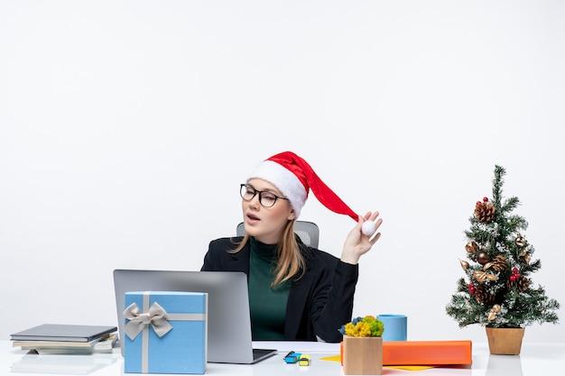 Mulher de negócios emocionalmente animada brincando com um chapéu de papai noel, sentada à mesa com uma árvore de natal e um presente nela e verificando seus e-mails no fundo branco
