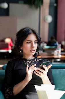 Mulher de negócios encantador tomando café e usando telefone celular no café café.