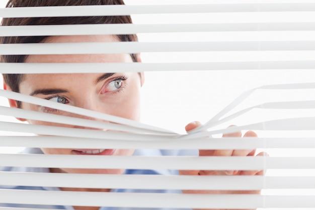 Mulher de negócios encantadora que olha através de um cortina veneziana