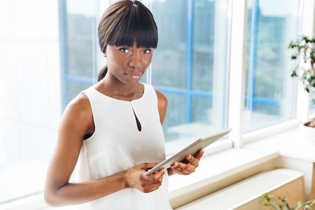 Mulher de negócios encantadora segurando um tablet e olhando para a frente no escritório